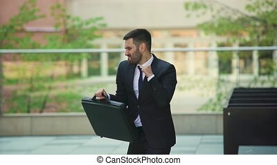 Attractive man with a beard and briefcase dancing in the...