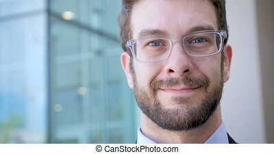 Attractive man with beard outside glass building smiling and...