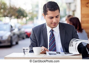 Attractive man with suit is resting in cafe