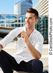 attractive man with sunglasses sitting in city