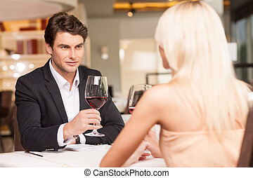 Attractive man with wine glass looking at beautiful woman. Trying to seduce