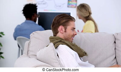 Attractive man lying on couch working on laptop
