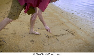 Attractive man writes I Love You in the sand on the beach with a stick