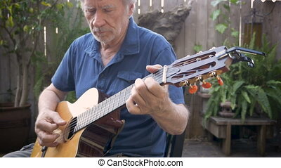 Attractive mature senior man performing a musical song on acoustic guitar