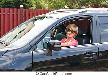 attractive mature woman in a car