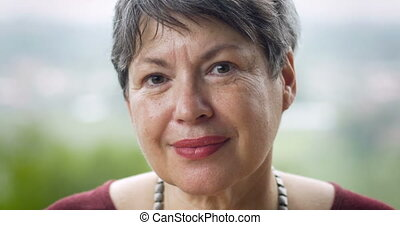 Attractive mature woman in her 60s smiling portrait -...