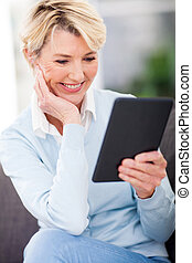 mature woman reading a book on tablet computer