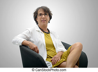 attractive mature woman sitting on a black chair