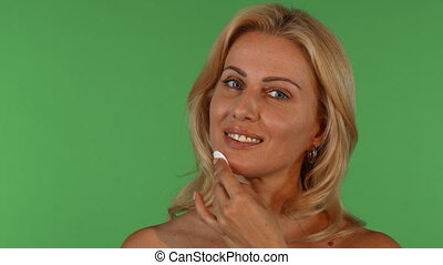 Attractive mature woman wiping her face with a cotton pad