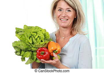 Attractive mature woman with salad and paprika