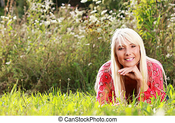 Attractive matured woman lying in the grass