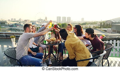 Attractive men and women are toasting and clinking glasses and bottles then drinking beer and cocktails and laughing during party on rooftop in modern city.