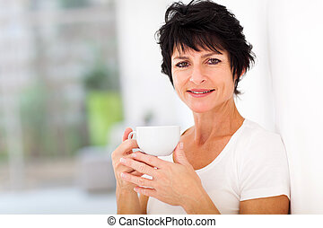 attractive mid age woman enjoying coffee