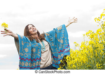 Attractive middle age woman with arms outstretched in flower...