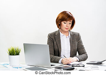 Attractive middle aged businesswoman writing