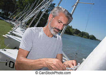 attractive middle-aged man preparing sport sailboat