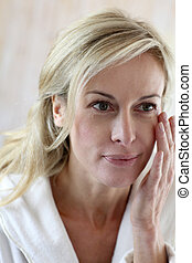 Attractive middle-aged woman applying cosmetics on her face