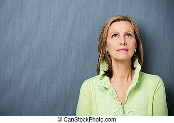 Attractive middle-aged woman daydreaming