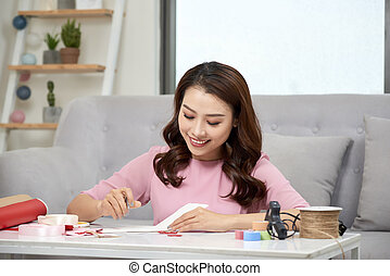 attractive middle aged woman scrapbooking at home