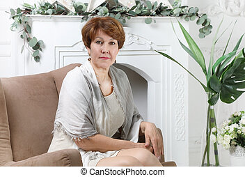 Attractive middle aged woman sitting in a chair