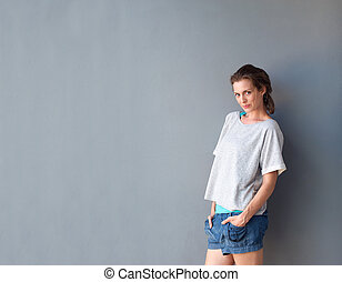 Attractive middle aged woman standing against gray background