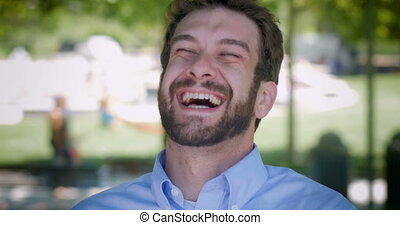 Attractive millennial man in 30s with beard laughing out...