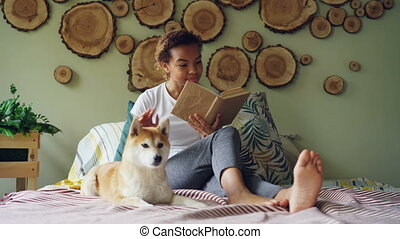 Attractive mixed race girl is reading book and stroking her puppy sitting barefoot on bed in modern apartment. Loving animals, enjoying literature and houses concept.