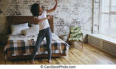 Attractive mixed race joyful girl have fun dancing near bed...