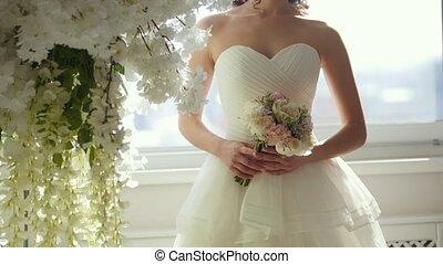 Attractive model in wedding dress with bride's bouquet