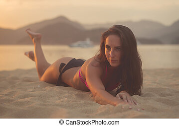 Attractive model with brown hair wearing bikini enjoying summer holidays lying on sandy beach at sunset sea and mountains in background