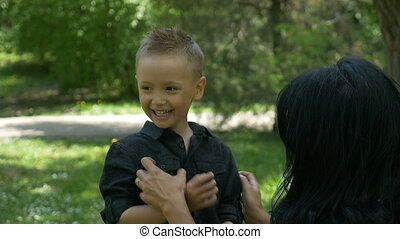 Attractive mom with black hair tickling her child and...