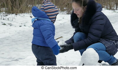Attractive mother and baby sculpts small snowman in the winter forest. Family fun for the Christmas holidays