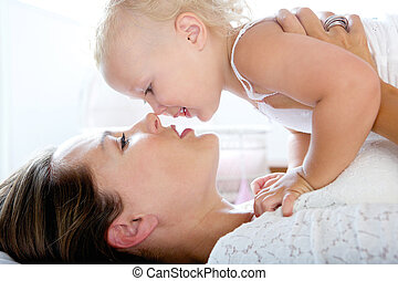 Attractive mother kissing cute baby girl