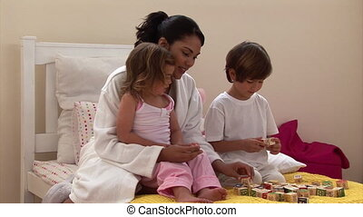Attractive mother playing with her children sitting on bed