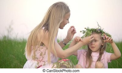 Attractive mother with her little daughter making a heart shape with their hands sitting on the grass in summer meadow