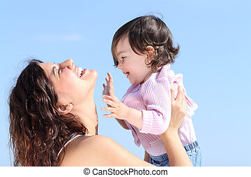 Attractive mum raising her daughter and playing together