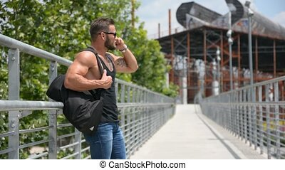 Attractive muscleman using cell phone