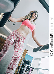 Attractive muscular fitness woman running on nordic ski in gym