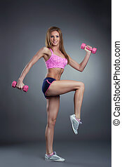 Attractive muscular girl exercising with dumbbells