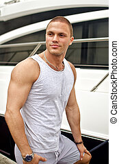 Attractive muscular male near the yacht