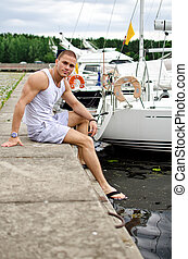Attractive muscular male sitting near the yacht