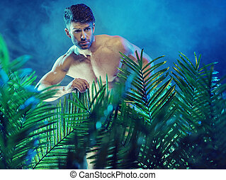 Attractive muscular man in the jungle