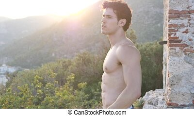 Attractive muscular shirtless young man in nature