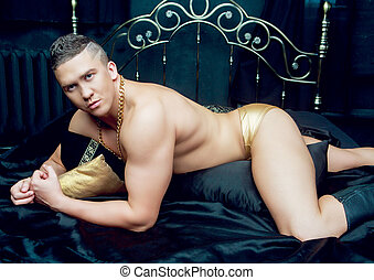 young man in bed - attractive muscular young man in bed with...