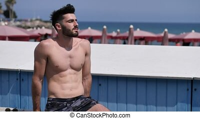 Attractive muscular young man on seaside promenade -...