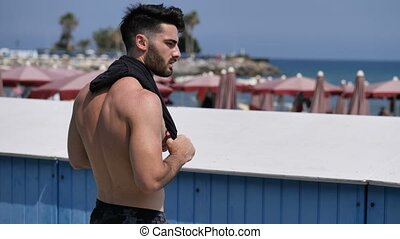 Attractive muscular young man on seaside promenade