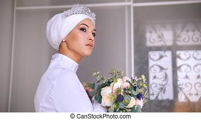 Attractive muslim bride with professional make up in wedding dress with bouquet of flowers