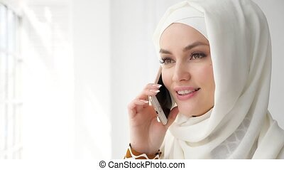 Attractive muslim woman in hijab is talking mobile phone. -...