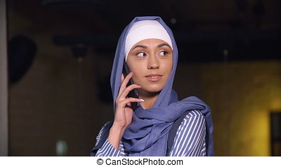 Attractive Muslim woman in hijab talking at mobile phone -...