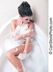 Attractive naked girl enjoys a bath